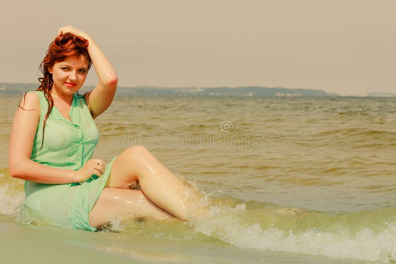 Женщина Redhead представляя в воде во время летнего времени стоковая фотография