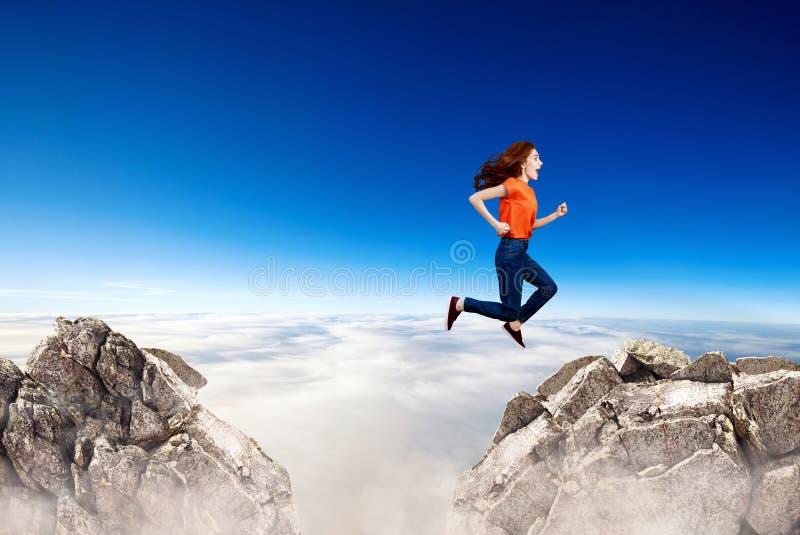 Женщина Redhead скачет через зазор между холмами стоковое изображение rf