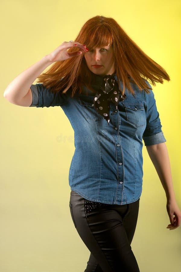 Женщина Redhead смотря подозрительную желтую предпосылку стоковое изображение