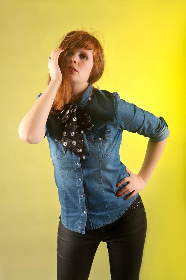 Женщина Redhead смотря сексуальную желтую предпосылку стоковая фотография
