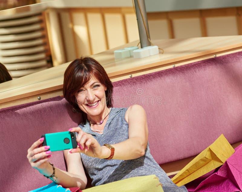 Женщина Shopaholic делая selfie стоковые фотографии rf