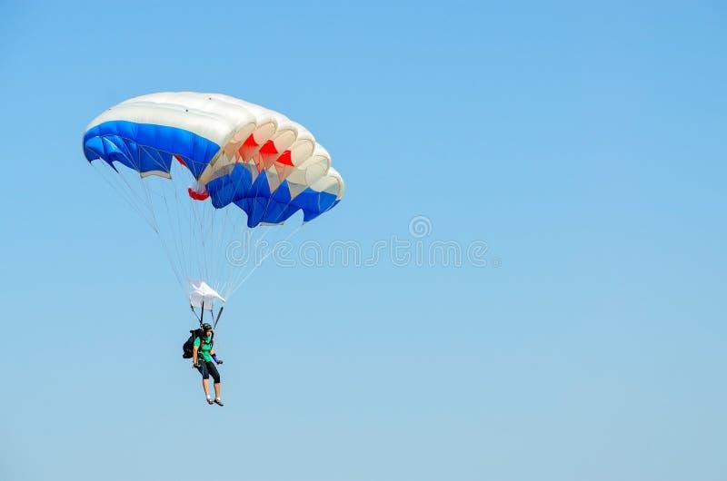 Женщина - skydiver выполняет спуск против безоблачного голубого неба стоковые фото