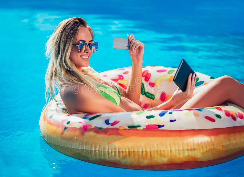 Женщина suntan Njoying в бикини на раздувном тюфяке в бассейне используя цифровые планшет и кредитную карточку стоковое изображение