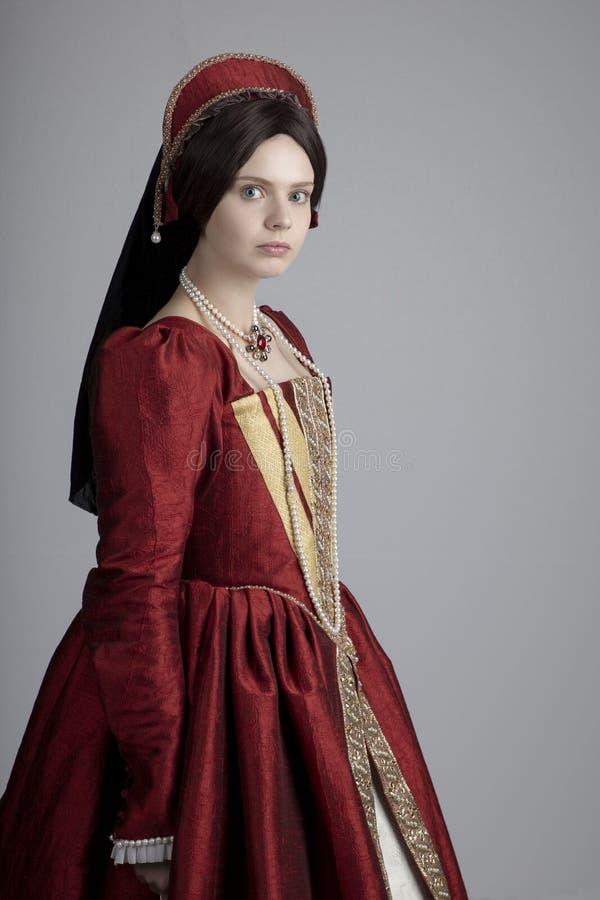 Женщина Tudor в красном платье стоковые изображения