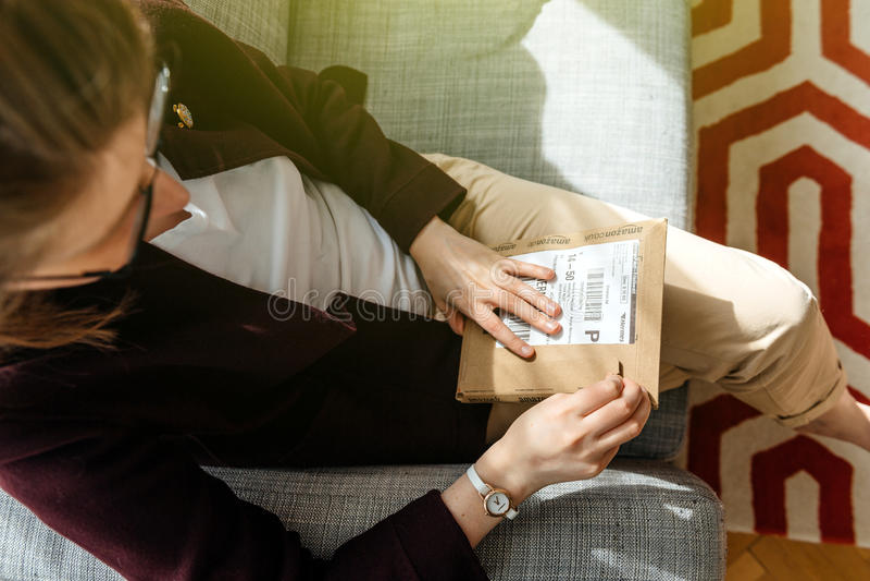 Женщина unboxing распаковывающ Амазонку com кладет в коробку стоковые фото