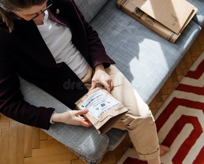 Женщина unboxing распаковывающ Амазонку com кладет в коробку стоковая фотография rf