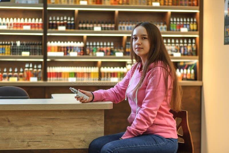 Женщина Vape Молодая милая девушка в розовом hoodie куря электронную сигарету стоковое фото rf