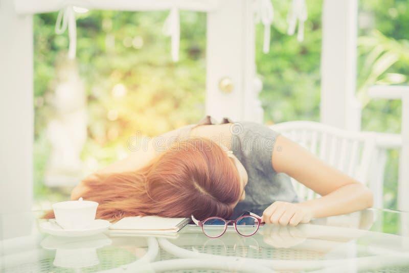 Женщина Workhard молодая азиатская попробовала и сон на столе в саде стоковое фото rf