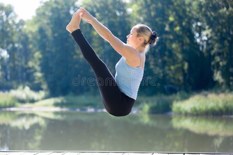 Женщина Yogi делая двойное владение пальца ноги в среднем воздухе стоковая фотография