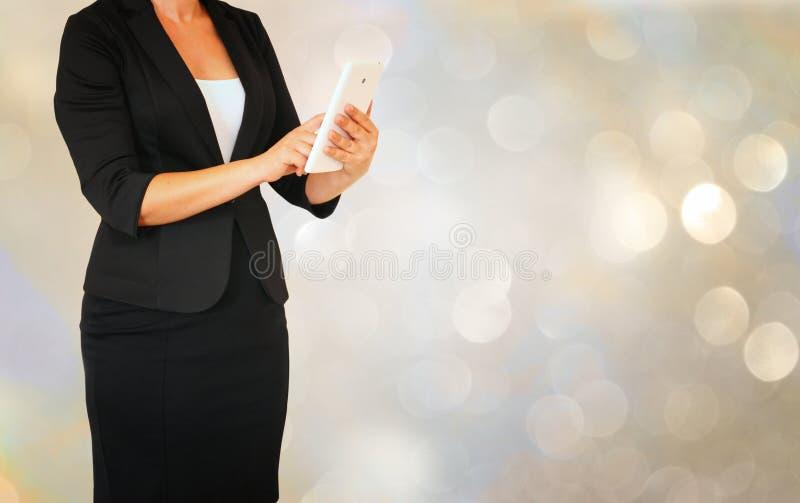 Женщина Younf элегантная в деловом костюме держа таблетку перед bokeh glamourus освещает предпосылку стоковое изображение rf