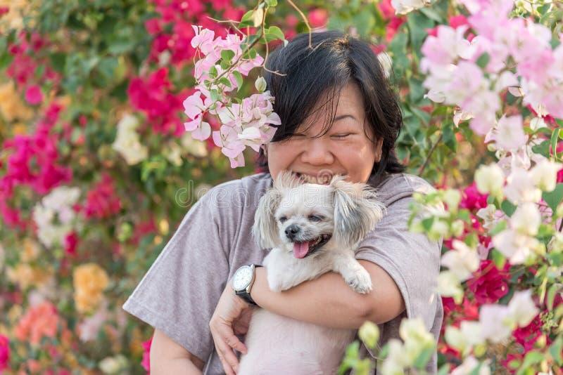 Женщины Азии и обнимать улыбки собаки счастливый стоковая фотография