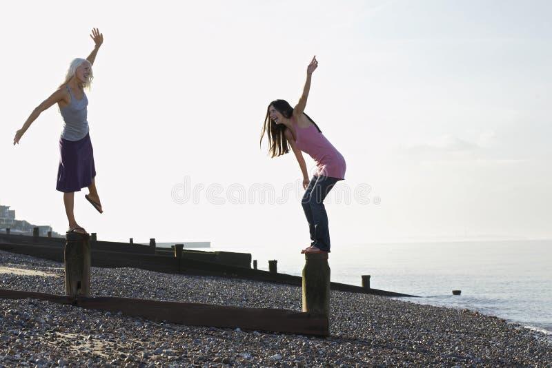 Женщины балансируя на выключателях волны на пляже стоковые фотографии rf