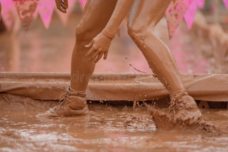 Женщины бегуна гонки грязи вползая в грязи под препятствиями стоковые изображения rf