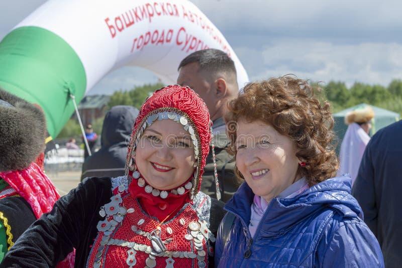 2 женщины взрослые, одно из их в Bashkir национальном костюме, другой нет, на мусульманском фестивале стоковое фото rf