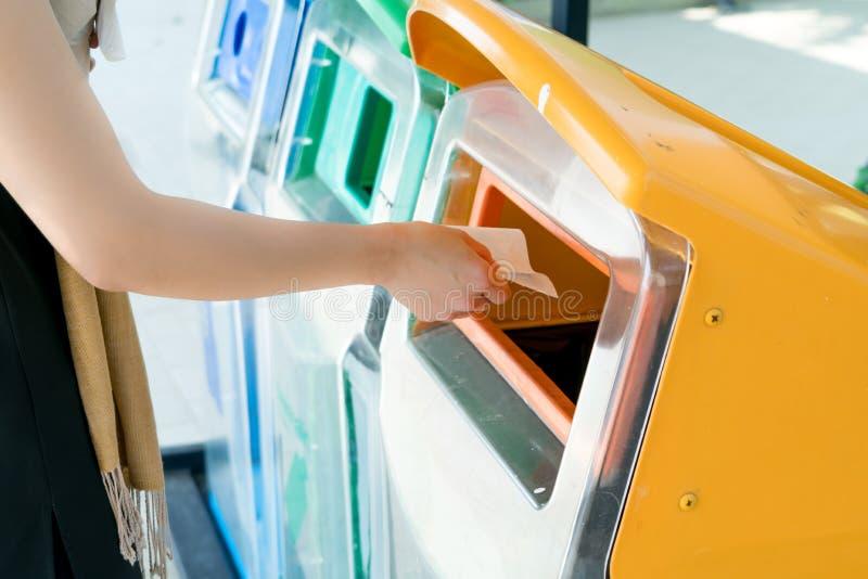 Женщины вручают бросать прочь отброс к ящику/погани, сортируя отход/отброс перед падением к ящику стоковые изображения