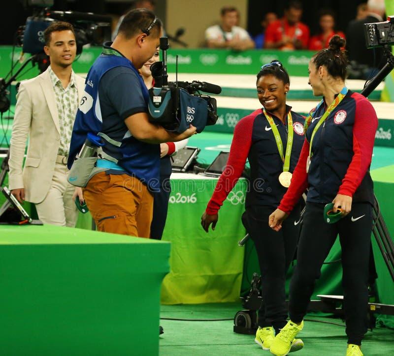 Женщины все-вокруг медалистов гимнастики на Рио 2016 желчей Simone Олимпийских Игр США (l) и Aly Raisman США стоковая фотография