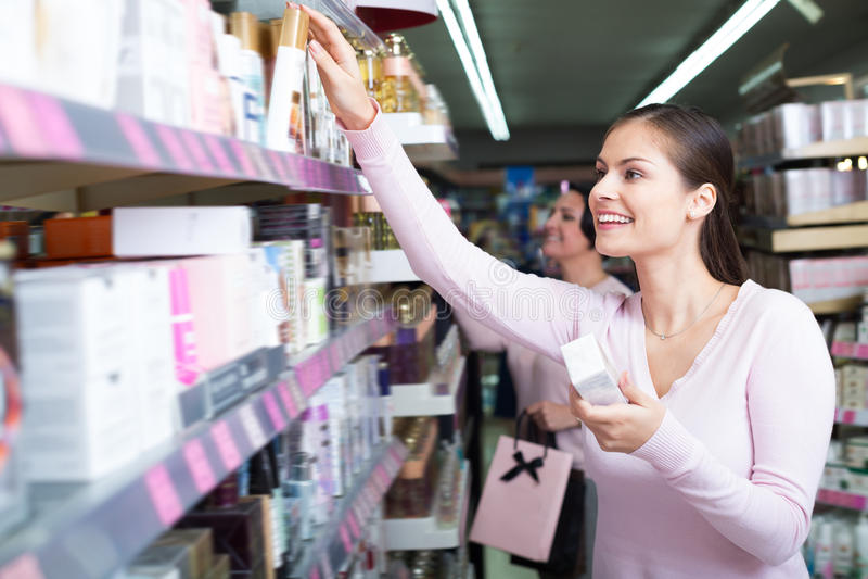 Женщины выбирая сливк от полки стоковое фото rf