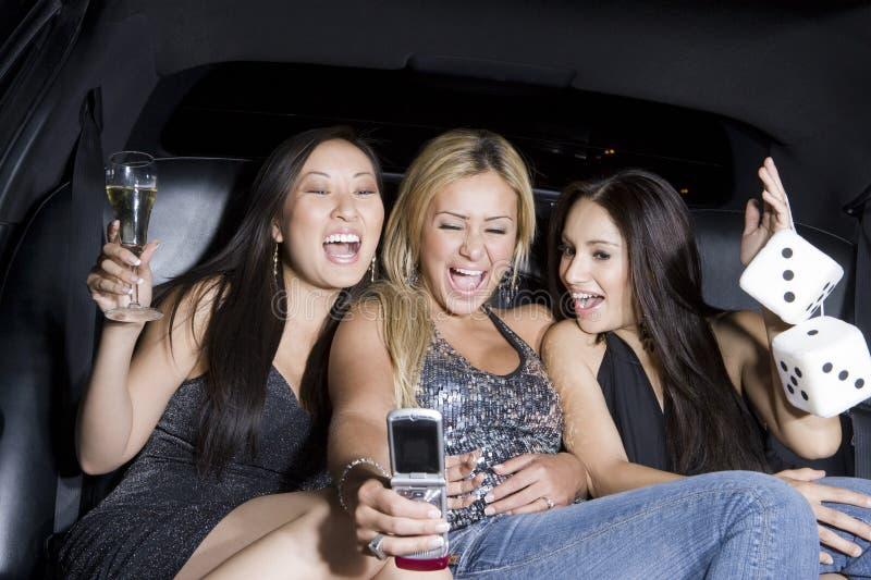 Женщины в лимузине принимая автопортрет через мобильный телефон стоковое изображение rf
