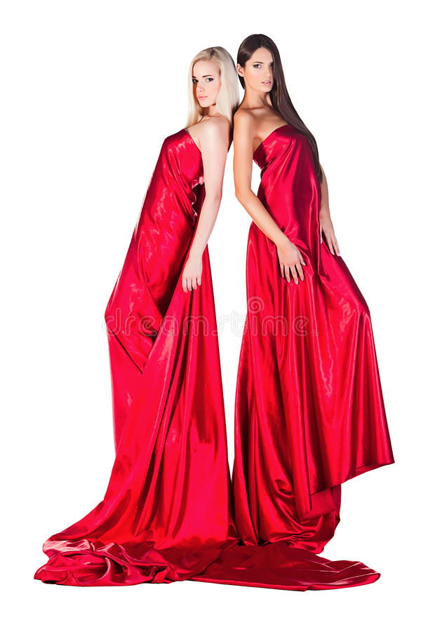 2 женщины в красном платье стоя спина к спине стоковые фотографии rf