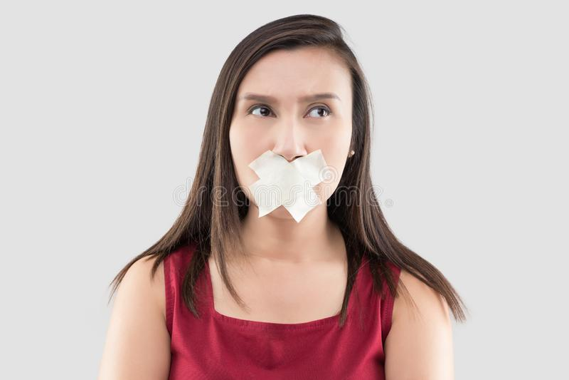 Женщины в красных платьях используют ленту для маскировки для того чтобы закрыть рот потому что они не хотят комментировать стоковые фото
