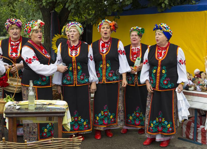 Женщины в национальных украинских костюмах поют песню стоковые фото