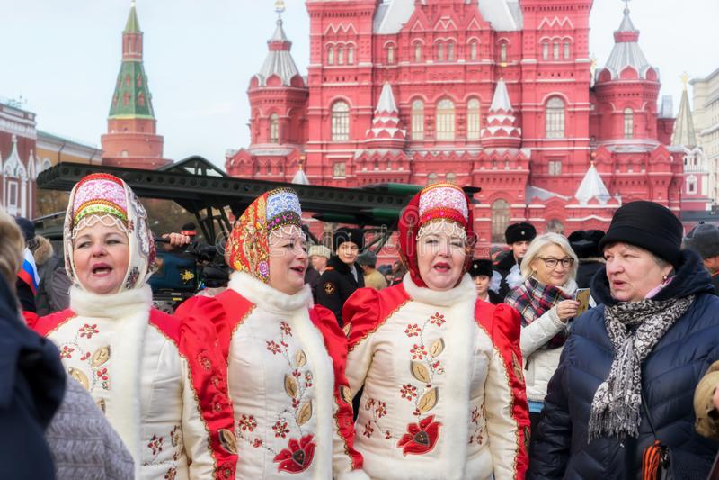 Женщины в традиционных национальных костюмах поют в красной площади стоковое фото rf