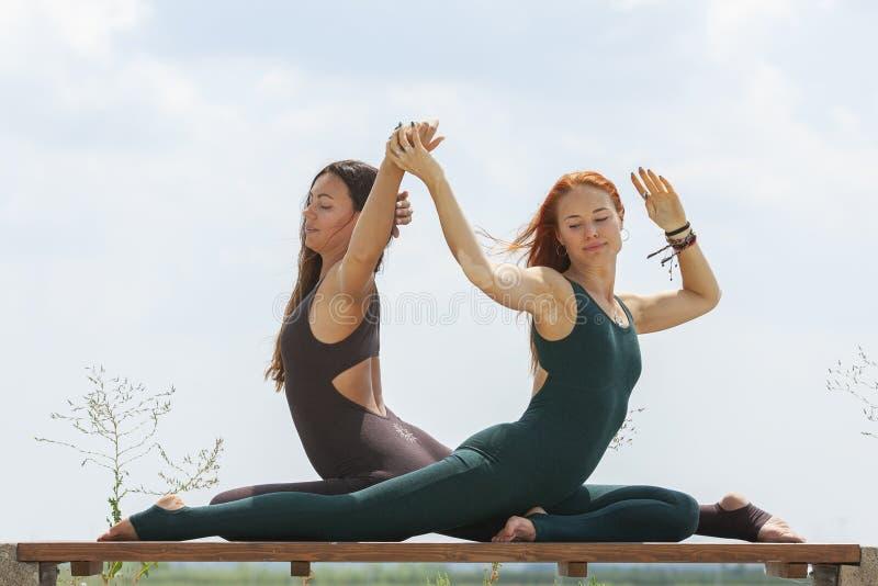 2 женщины делая йогу outdoors инструктор йоги показывает представления стоковые изображения