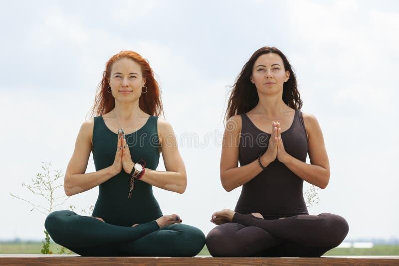 2 женщины делая йогу outdoors инструктор йоги показывает представления стоковая фотография rf