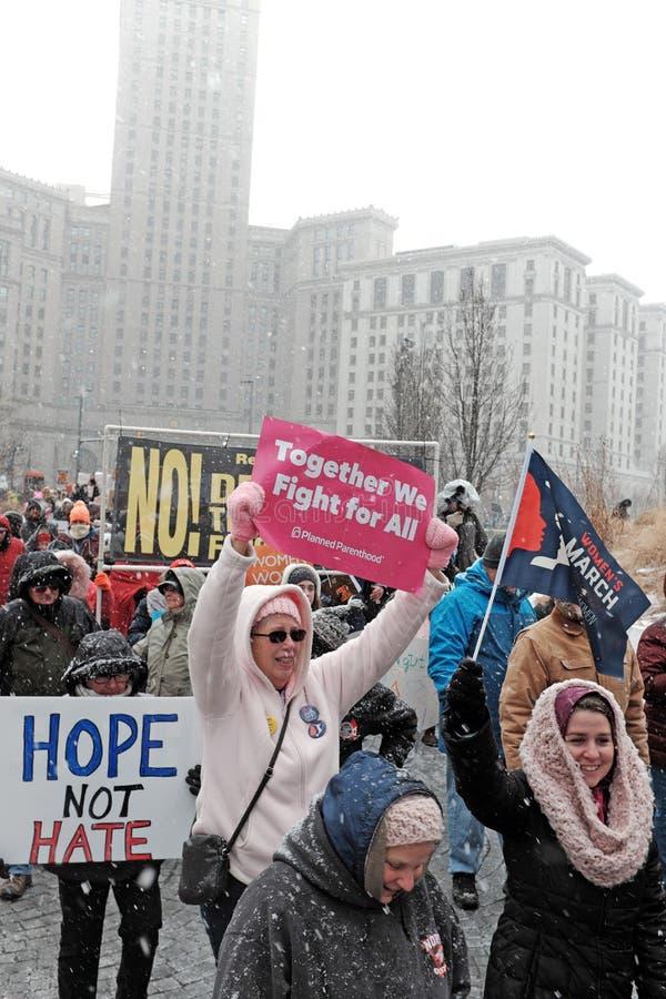 Женщины держат знаки по мере того как они маршируют в март 2019 женщин в Кливленд, Огайо, США стоковое фото rf