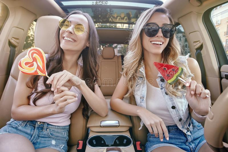 Женщины держа большие леденцы на палочке в автомобиле стоковые изображения