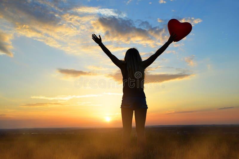 Женщины держа воздушный шар в форме сердца в руке на заходе солнца стоковое изображение