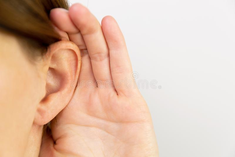 Женщины держа руку к уху Слышать секрет стоковые фото