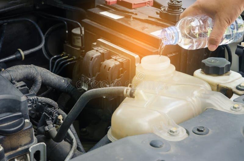 Женщины заполняя воду к радиатору автомобиля концепция для безопасности перед t стоковое изображение