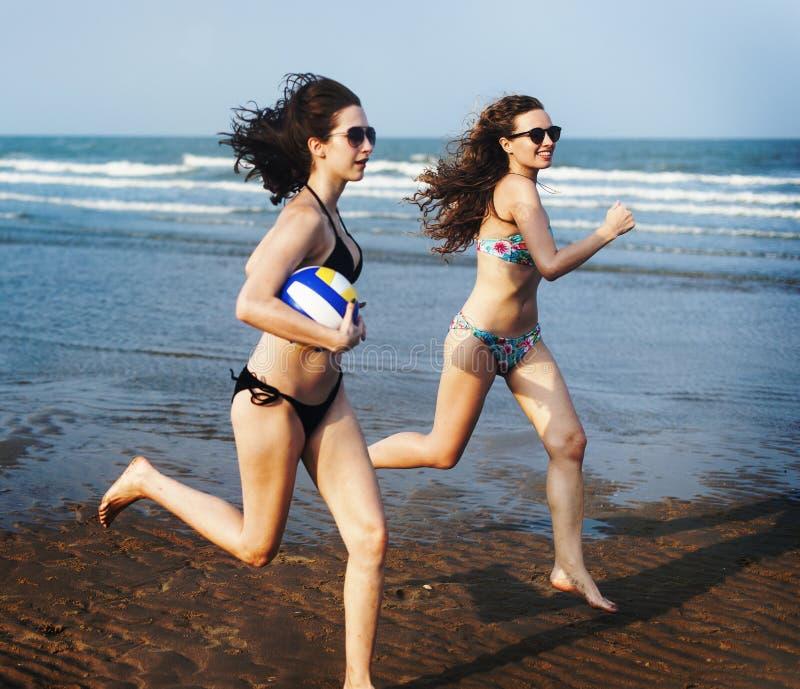 Женщины играют шарик пляжа стоковое фото