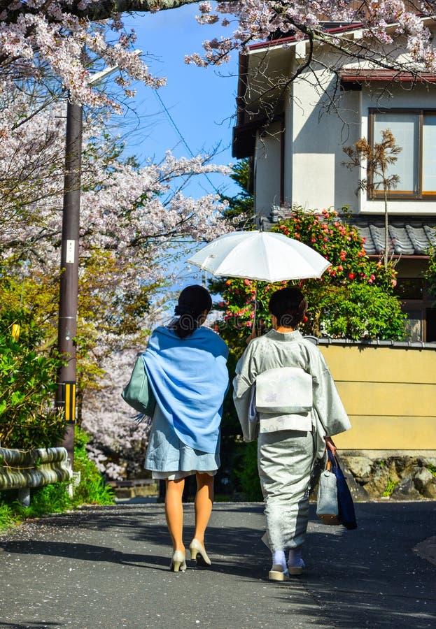 Женщины идя под вишневые цвета стоковая фотография rf