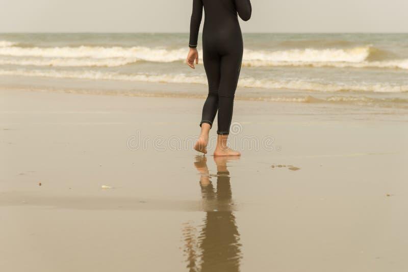 Женщины идя самостоятельно на пляж перемещение пляжа на временени стоковое изображение