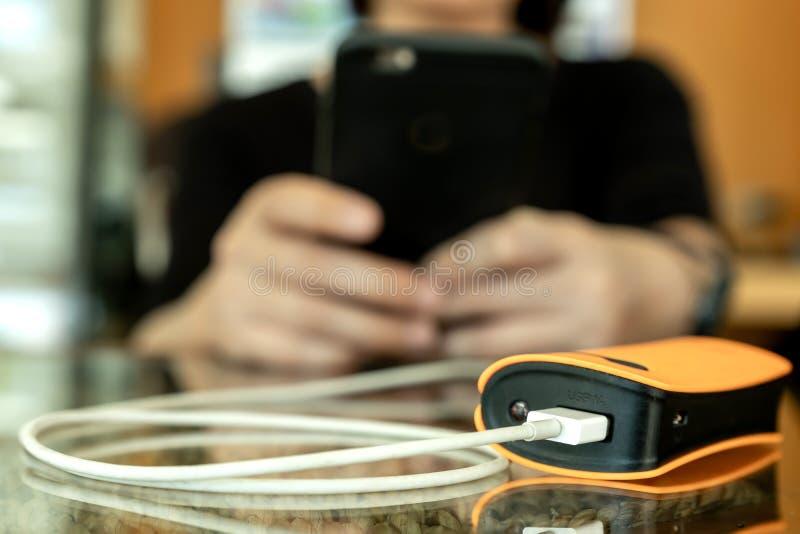 Женщины используют банк силы для умный поручать телефона стоковые фотографии rf