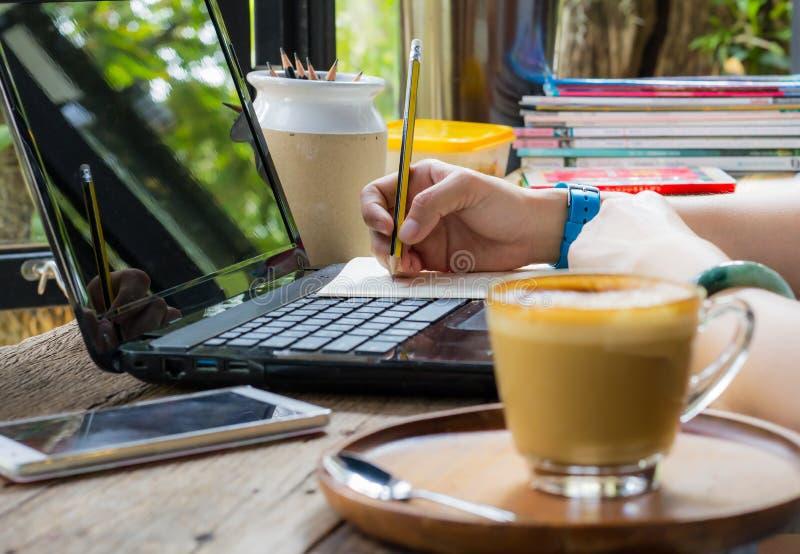 Женщины используют карандаш для записи книг Установленный на компьютер-книжке на деревянном столе Имейте кофе и smartphone как не стоковые фотографии rf