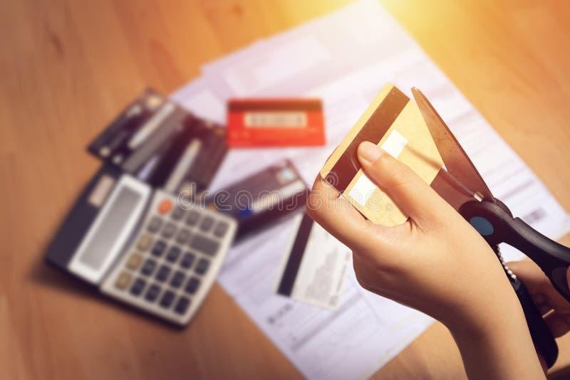 Женщины используют ножницы для того чтобы отрезать кредитные карточки в руке с много кредитная карточка и заявление на таблице дл стоковая фотография rf