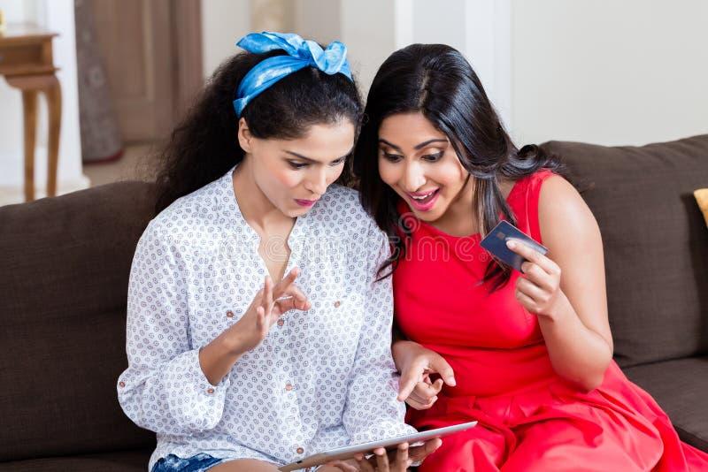 2 женщины используя ПК таблетки для онлайн оплаты стоковое фото