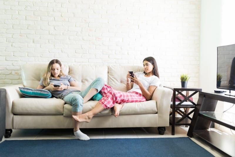 Женщины используя Smartphones и игнорирующ один другого во время Sleepover стоковое фото rf