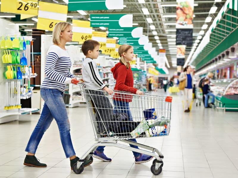 Женщины и дети с покупками тележки стоковые изображения