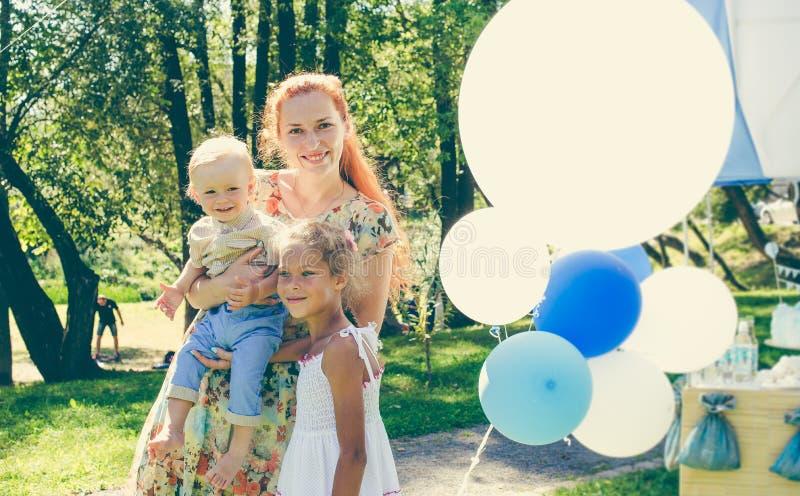 Женщины и 2 дето- мальчик и девушка около воздушных шаров Летний день на пикнике в парке города стоковые фотографии rf