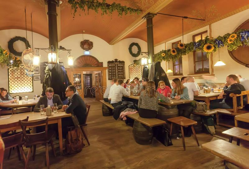 Женщины и люди есть и выпивая пиво внутри традиционного ресторана в старом баварском стиле стоковая фотография