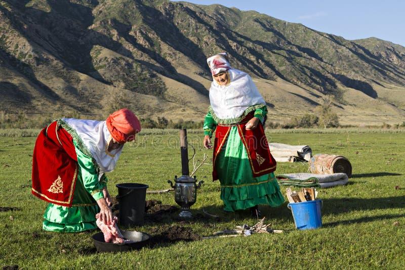 Женщины казаха в национальных костюмах варя мясо, в деревне Saty, Казахстан стоковое изображение rf