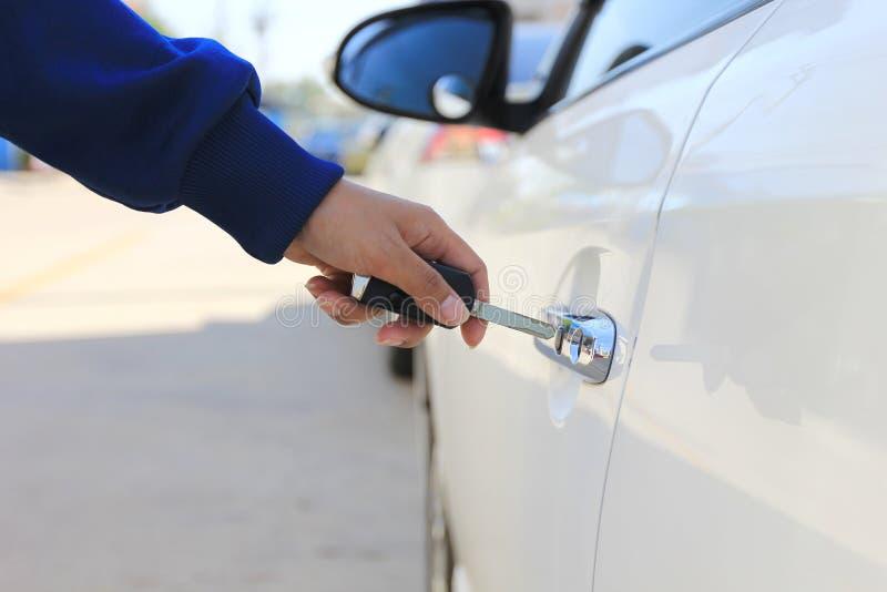 Женщины крупного плана вручают ключ автомобиля удерживания к открывая или раскрывая автомобильной двери стоковое изображение