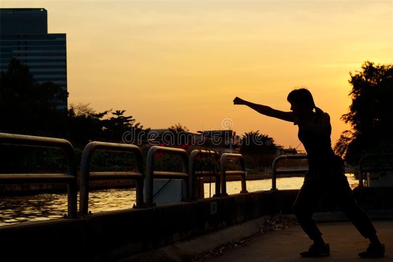 Женщины кладя силуэт в коробку тренировки и боевых искусств на заходе солнца стоковые изображения rf