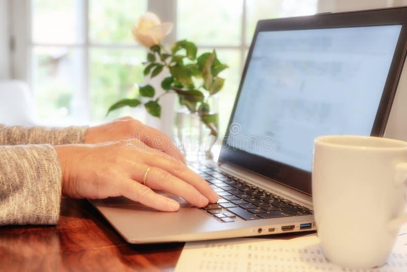 Женщины ласкают ноутбук дома, чтобы проверить электронную почту и социальные сети, или просматривают интернет для получения инфор стоковые фотографии rf