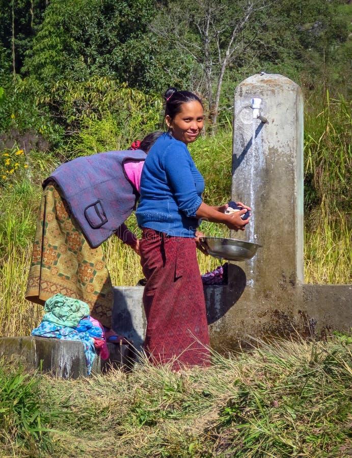 Женщины моя одежды на общественном водопроводном кране в небольшом горном селе, Непале стоковые изображения rf