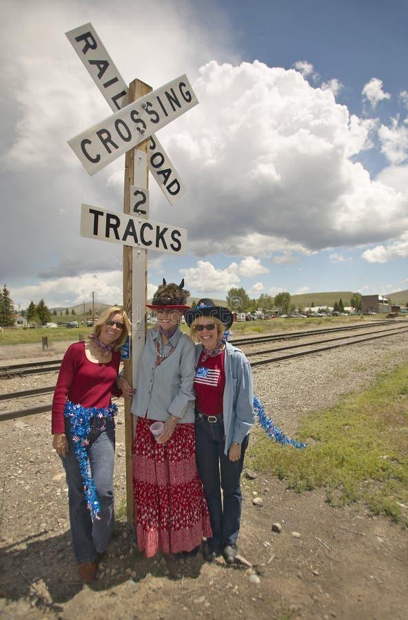 3 женщины на железнодорожном переезде одели для четверти от июля, в Лиме Монтане стоковая фотография